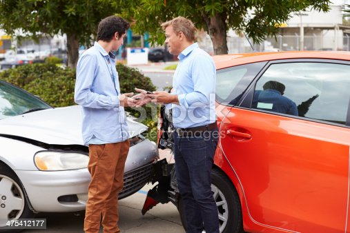 475395935istockphoto Two Drivers Exchange Insurance Details After Accident 475412177