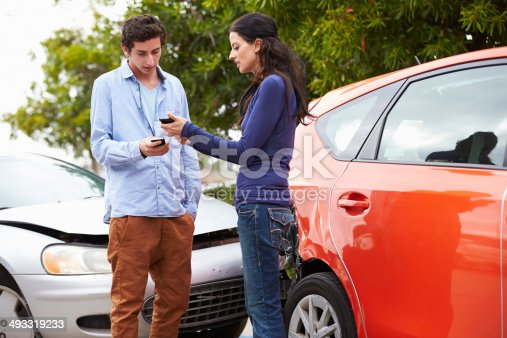 475395935istockphoto Two Drivers Exchange Insurance Details After Accident 493319233