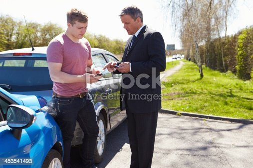 475395935istockphoto Two drivers exchanging details after a minor car collision 453541493