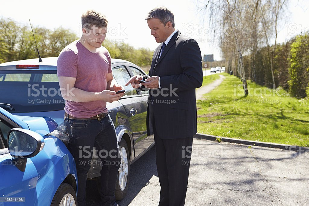 Two drivers exchanging details after a minor car collision stock photo