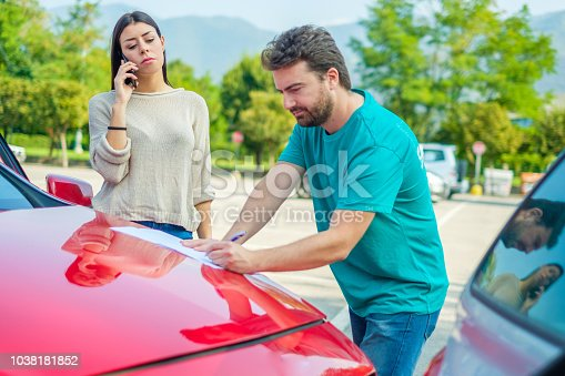 1047083324 istock photo Two drivers filling the accident report document after car crash 1038181852