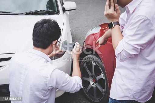 istock Two drivers man arguing after a car traffic accident collision and making phone call to Insurance Agent and take a photo, Traffic Accident and insurance concept 1131993277