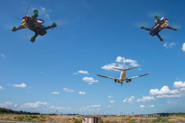 Two drones flying near an airplane stock photo