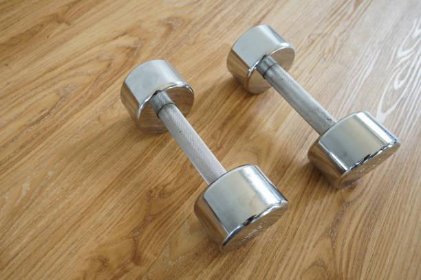 zwei kurzhanteln für fitness auf holzboden. - killer workouts stock-fotos und bilder