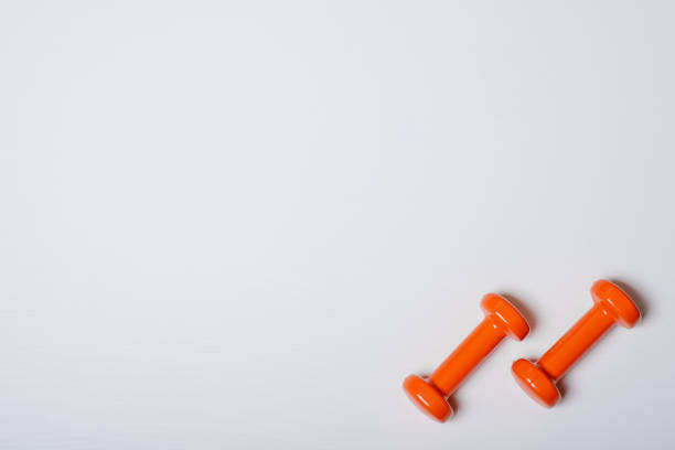 Two dumbbells of orange are lying on a white background with a tree texture stock photo