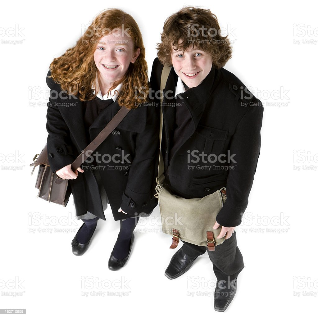 Two early teenage students in full uniform with satchels royalty-free stock photo