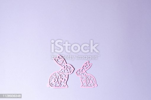istock Two Easter bunny cut out of pink paper. 1128936348