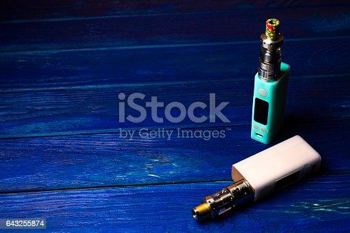 864217444 istock photo two e-cigarette (electronic cigarette, vape) on the wood background 643255874