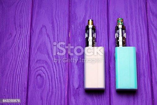 864217444 istock photo two e-cigarette (electronic cigarette, vape) on the wood background 643255876
