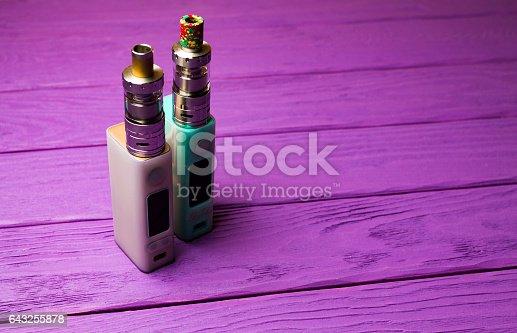 864217444 istock photo two e-cigarette (electronic cigarette, vape) on the wood background 643255878