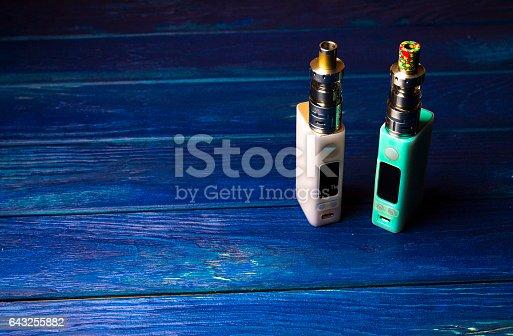 864217444 istock photo two e-cigarette (electronic cigarette, vape) on the wood background 643255882