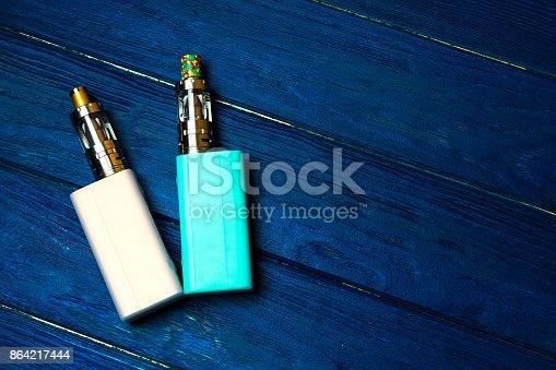 864217444 istock photo two e-cigarette (electronic cigarette, vape) on the wood background 864217444