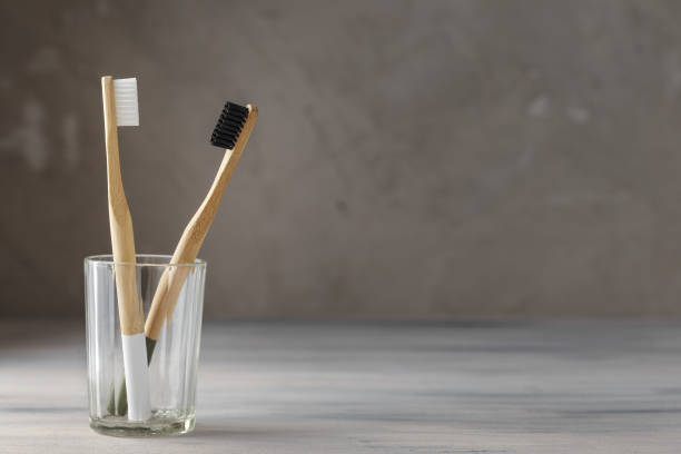 Two eco friendly bamboo tooth brushes in a glass Two eco friendly bamboo tooth brushes in a glass. Zero Waste concept. Copy space for text toothbrush stock pictures, royalty-free photos & images