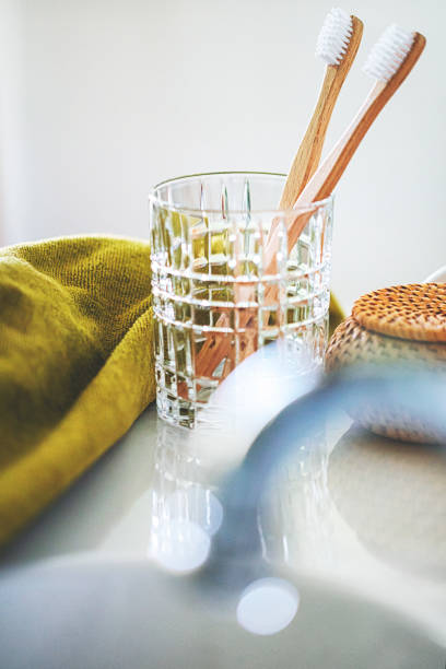 Two eco-friendly wooden toothbrushes in the glass stock photo