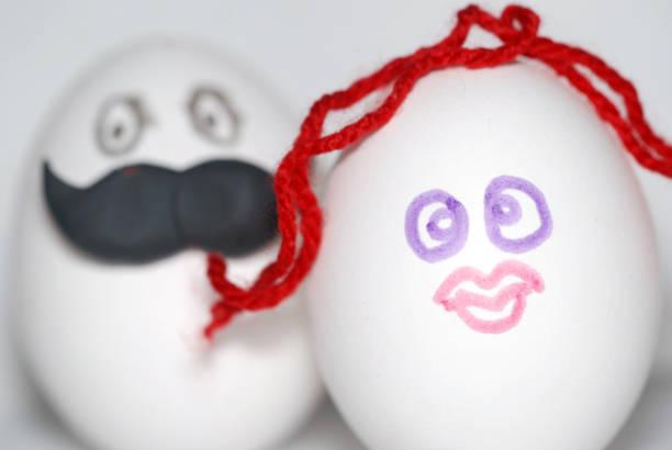 zwei eier unter einem mann im hintergrund dekoriert, mit einem großen schnurrbart und eine frau im vordergrund, mit roten haaren, als braut und bräutigam, ein paar konzept - liebesbeweis für ihn stock-fotos und bilder