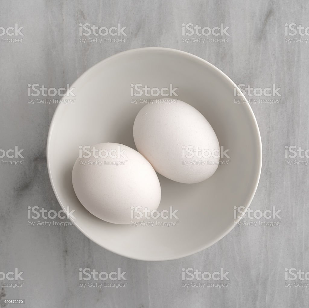 Two eggs in a bowl atop a marble cutting board. zbiór zdjęć royalty-free