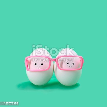 istock Two eggs in pink glasses like Siamese twins 1127072378