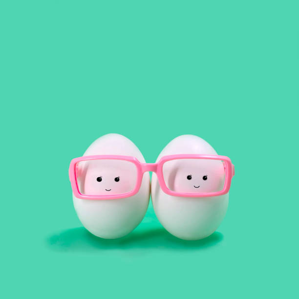 Two eggs in pink glasses like Siamese twins stock photo