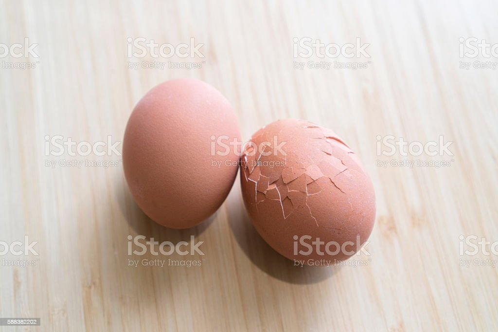 two eggs on table,one complete,one broken stock photo