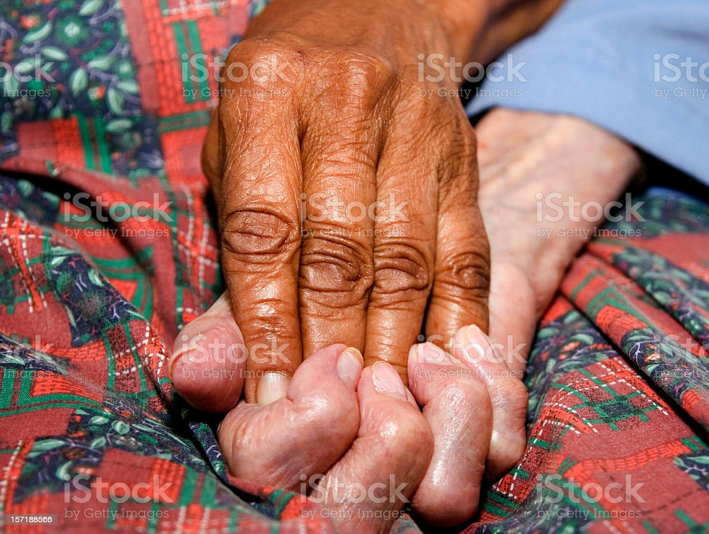 Two elderly hands grasped together in comfort and love stock photo