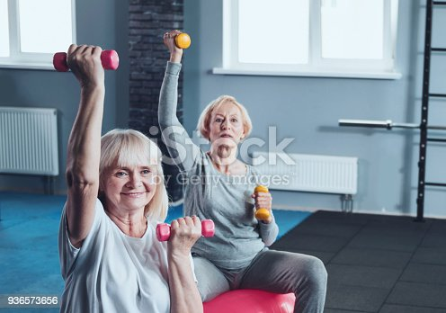 936573360 istock photo Two elderly ladies lifting weights while training in gym 936573656