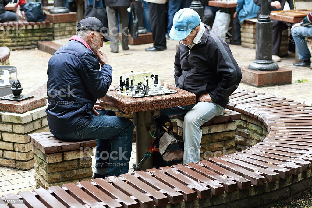 two elderly male retirees playing chess in the park. stock photo