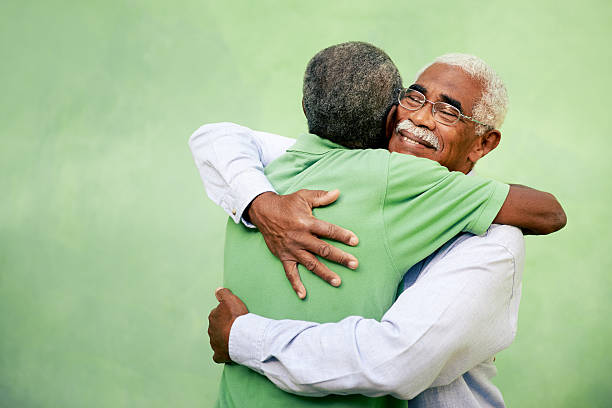 Two elderly men hugging on a green background Active retired old men and leisure, two senior black brothers hugging outdoors apologist stock pictures, royalty-free photos & images