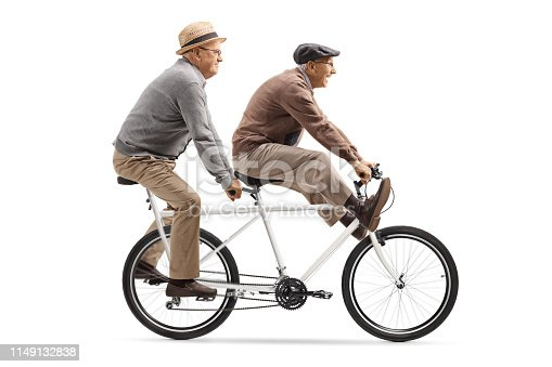 Full length shot of two elderly men riding a tandem bicycle with legs up isolated on white background