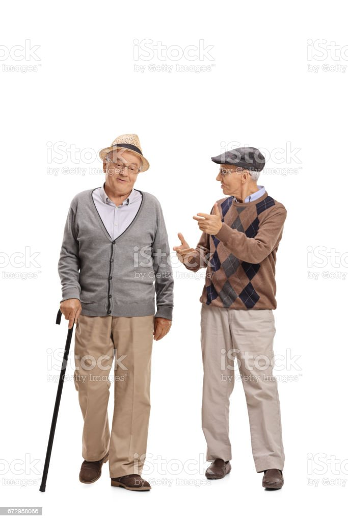 Two elderly men walking towards the camera and talking stock photo