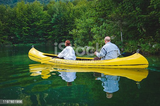 986720410 istock photo Two elderly persons canoeing in the lake 1197851956