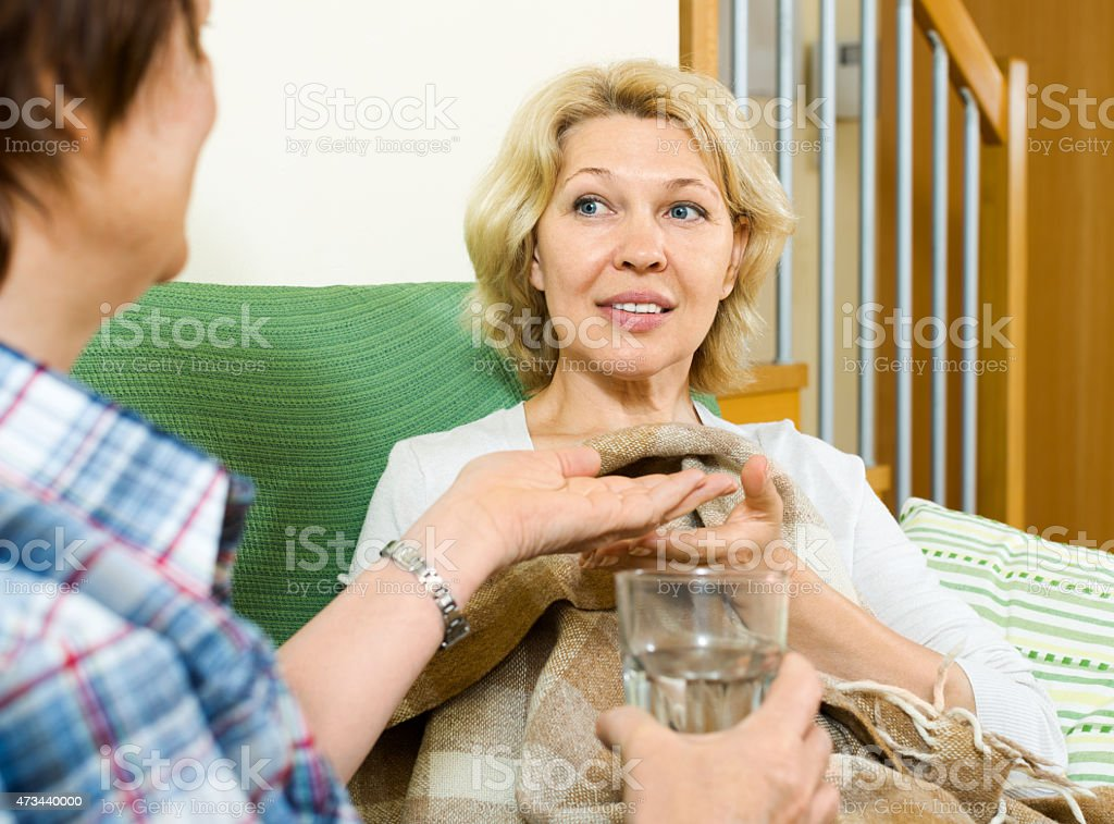 Two elderly women with pill and glass of water stock photo