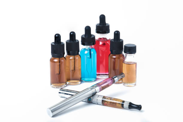 Two electronic cigarettes with glass e-liquid bottles on white background stock photo