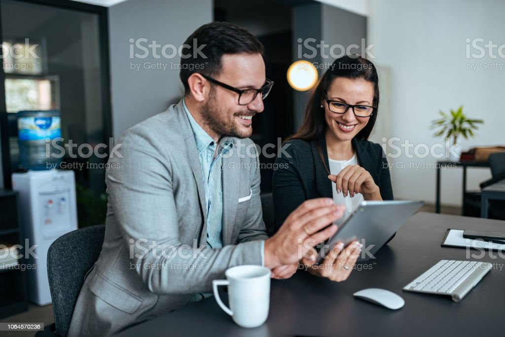 Two elegant business people smiling and looking at digital tablet. stock photo
