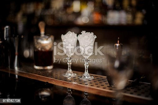 istock Two elegant cooled glasses filled with ice arranged on the bar counter 978282708