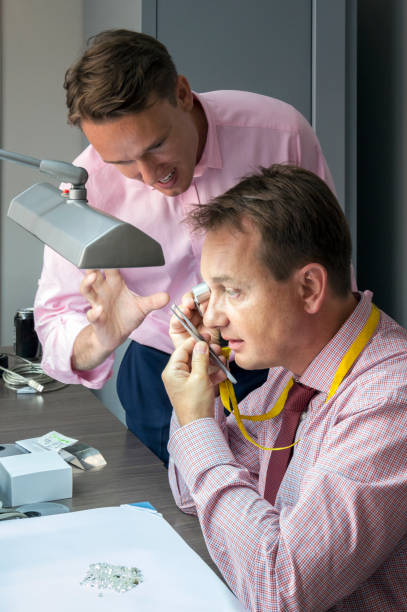 two elegant man checking quality of diamonds - diamanten kaufen stock-fotos und bilder