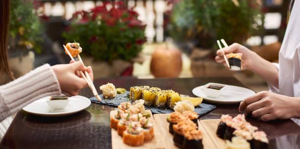 zwei elegante frauen essen sushi set mit wasabi und ingwer. - sushi essen stock-fotos und bilder