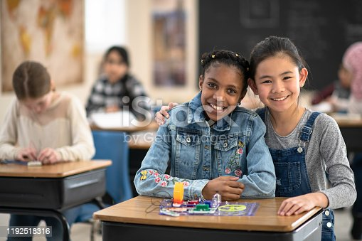 Two young elementary students sit together at a desk posing with their Stem project, for a portrait.  One student is of African decent and the other is Asian.  They are huddled in closely together and smiling.  They are seated among their multi-ethnic peers who are all dressed casually and also working away at their desks on a Stem project.