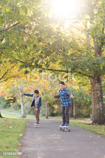 Two cheerful elementary age boys skate to school wearing backpacks. They are on a footpath in a forested public park on a beautiful autumn morning.
