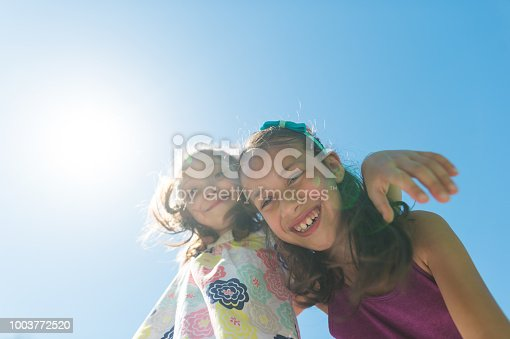Two young ethnic girls embrace and pose for the camera on a hot summer day. They are looking down as the camera shoots up at them.