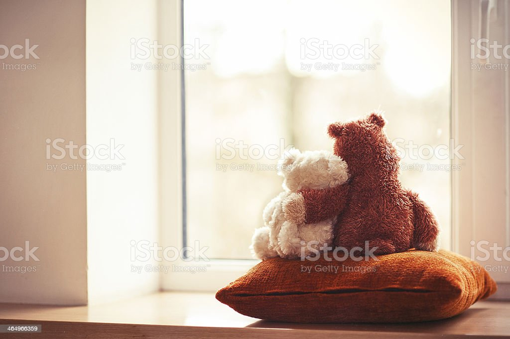 Two embracing teddy bears looking through the window sitting on...