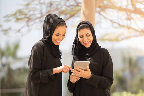 Two Emirati Women having discussion with a digital tablet stock photo