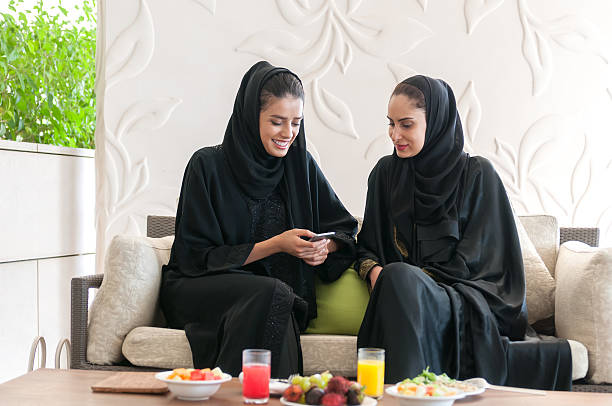 Two Emirati Women in Abaya Texting on Cellphone at Lunch stock photo