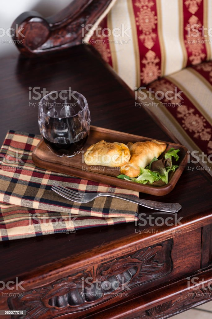 Two empanadas and a glass of wine in a chic retreat. 免版稅 stock photo
