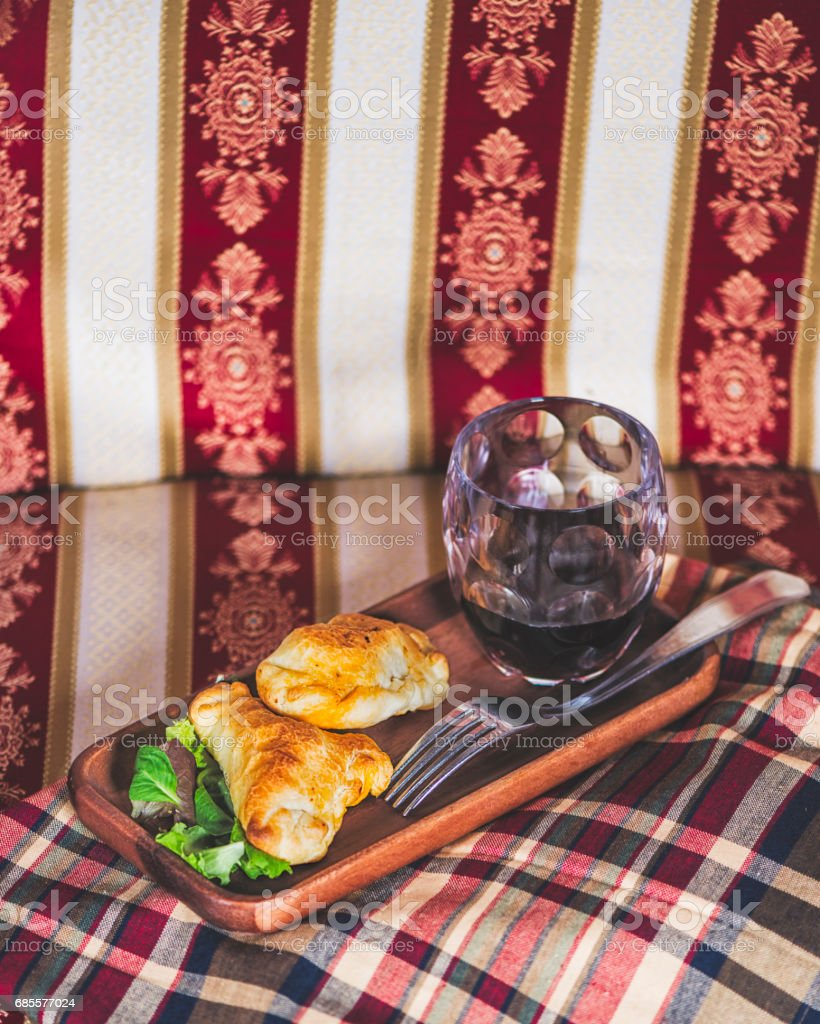 Two empanadas and a glass of wine in a chic retreat. royalty-free 스톡 사진