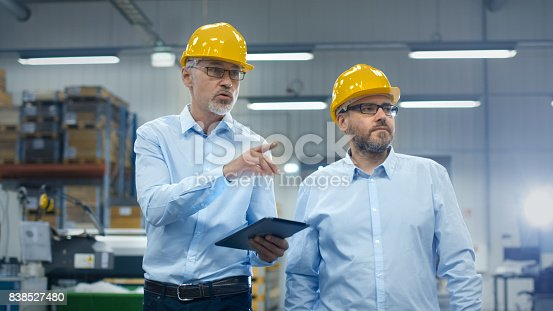 istock Two employees are walking with tablet computer at logistics center warehouse. 838527480