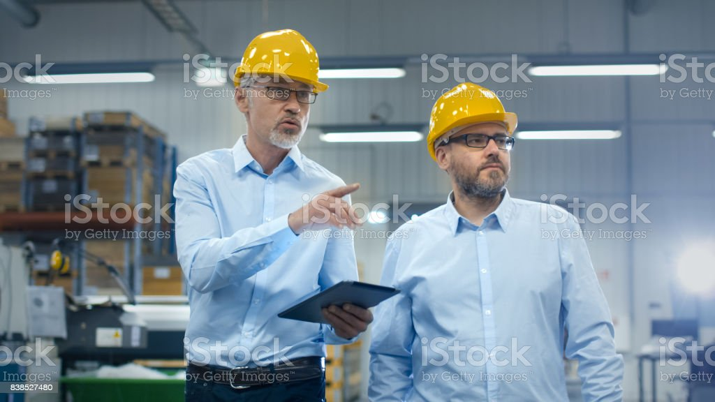 Two employees are walking with tablet computer at logistics center warehouse. stock photo