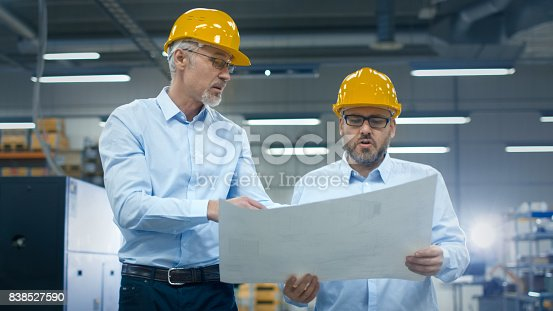 istock Two employees at logistics center warehouse talk about the plan on white paper. 838527590