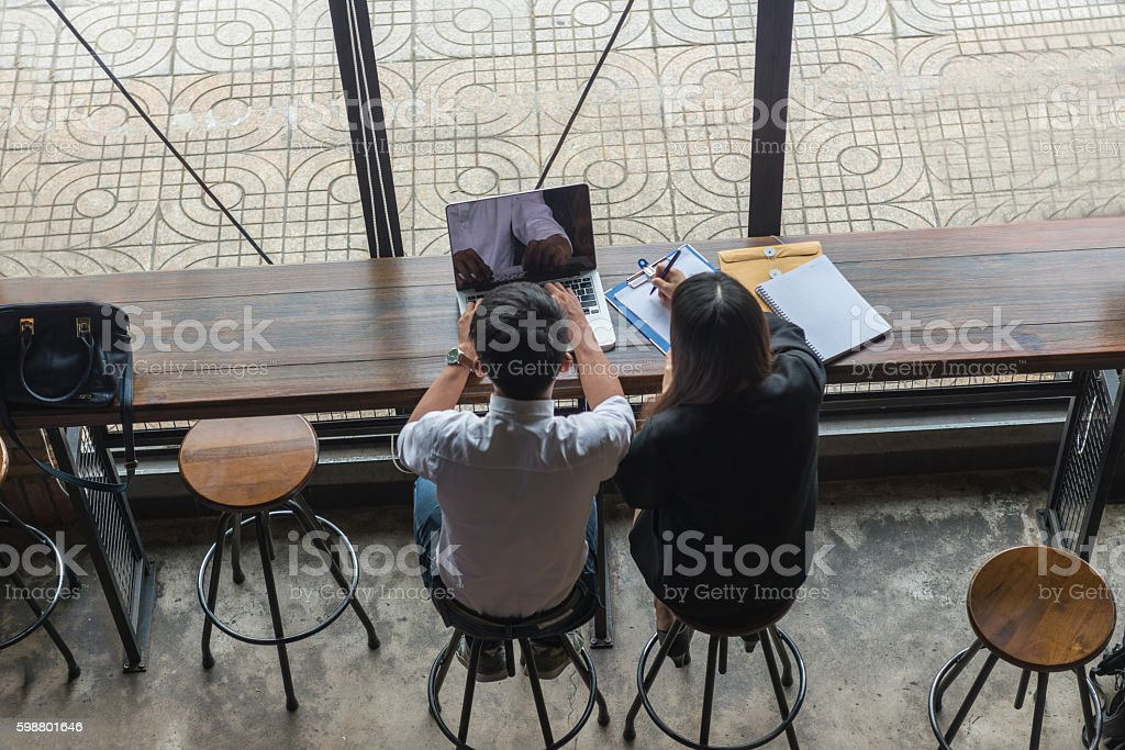 Two employees working with laptop, documents and having discussion stock photo