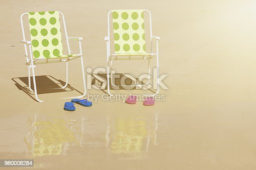 Two fold-up beach chairs and two pairs of sandals sit on an otherwise deserted and idyllic sunny beach, reflected in the damp sand.