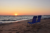 Looking to the sea two empty chairs on a sandy beach at sunset; Ionian coast, Greece
